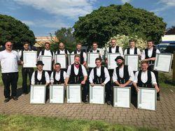 Verdient stolz zeigen die Jungdachdeckermeister des 2019er Jahrgangs ihre Meisterbriefe. Links ihr Ausbilder Gergely Wild.